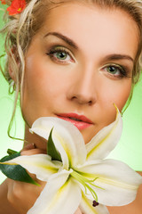 Beautiful young woman with lily flower. Close-up portrait