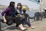 Two teens girl sitting on embankment. poster