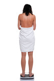 Woman in towel weighing herself poster