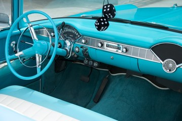 Interior shot of a blue colored 1956 convertible with fuzzy dice