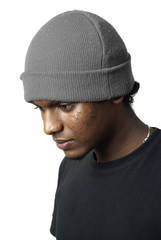 Indian man portrait with grey beanie hat looking down on white