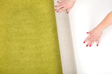 female hands unrolling a carpet