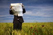 canvas print picture - businessman lost in field using a map