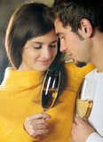 Young happy couple celebrating event with champagne poster