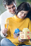 Young couple celebrating event with champagne and gifts poster