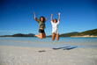 Two young women jumping on beach