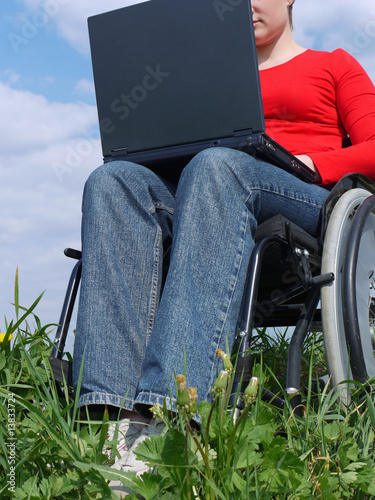 Handicapped woman on wheelchair using laptop outdoors