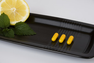 Yellow pills on black plate with lemon