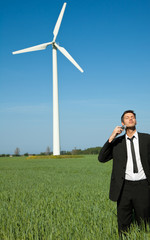 businessman shaving on meadow with ecology wind power