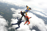 Four skydivers jump from a plane