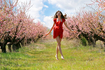 happy girl in red dress on spring garden and sky background