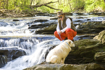 Man in River Looking Down at Dog
