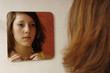 Mädchen betrachtet sich im Spiegel