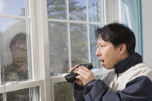 Man looking out a window with binoculars