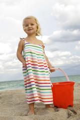 Girl holding a sand pail on the beach