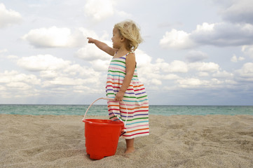 Girl holding a sand pail on the beach and pointing towards the sea