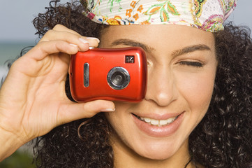 Close-up of a woman taking a picture with a digital camera