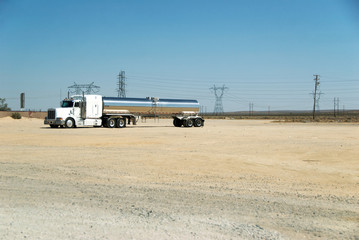 A Semi-Trailer Truck with a chrome gas tank by a desert highway