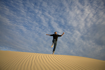 A man jumping off a sand dune
