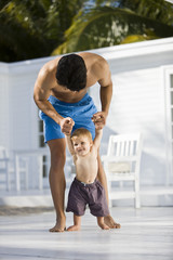 Man helping his son to walk
