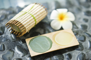 Close-up of a bar of soap with a flower and a tray of mud pack