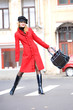 Girl in a red coat moves outdoors