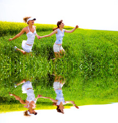 Two happy young women are runing in a field