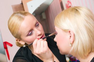 visagiste putting on models eye make up