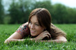 Young beautiful woman lays on green field