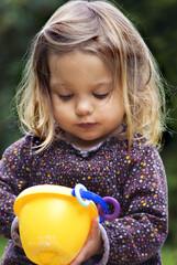 Mädchen spielt mit Eimer