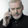 homme mûr contrarié au téléphone