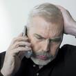 homme exaspéré au téléphone