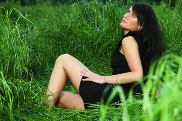 black haired girl woman in green fresh spring summer grass