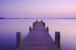 a blue sunset with a jetty over a lake with an evening glow