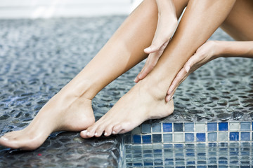 Woman rubbing her legs at the poolside