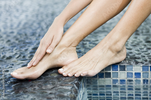 Woman rubbing her foot at the poolside