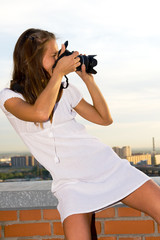 .A young girl on the roof of a skyscraper with a camera