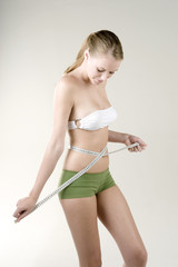 Woman measuring her waist with a tape measure