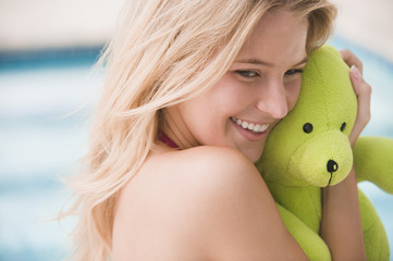 Close-up of a woman holding a teddy bear and smiling