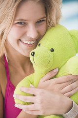 Portrait of a woman holding a teddy bear and smiling