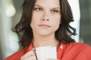 Woman holding a cup of tea and thinking