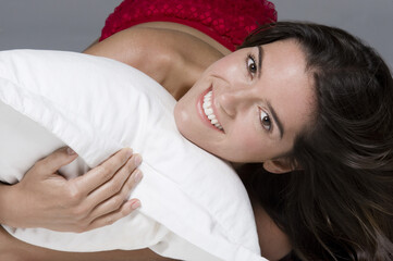 Portrait of a woman hugging a pillow and smiling