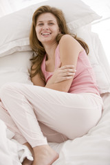 Woman resting on the bed and smiling