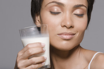 Close-up of a woman holding a glass of milk