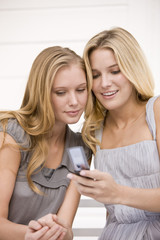Two women reading message on a mobile phone