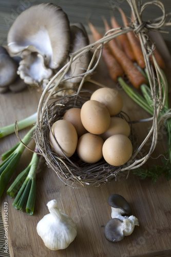 Fresh vegetables, eggs, and oyster mushrooms on a chopping block