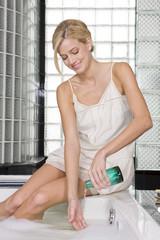 Woman pouring liquid soap in a bathtub