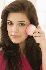 Woman applying blusher on her face