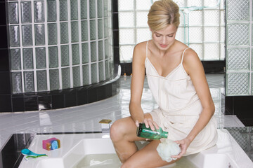 Woman pouring liquid soap on a loofah