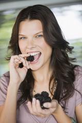 Portrait of a woman eating blackberries